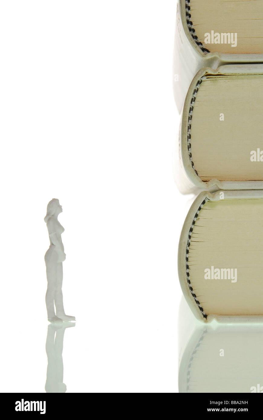 La figure d'une femme miniature avec curiosité debout en face d'une pile de livres, image symbolique de la connaissance Banque D'Images