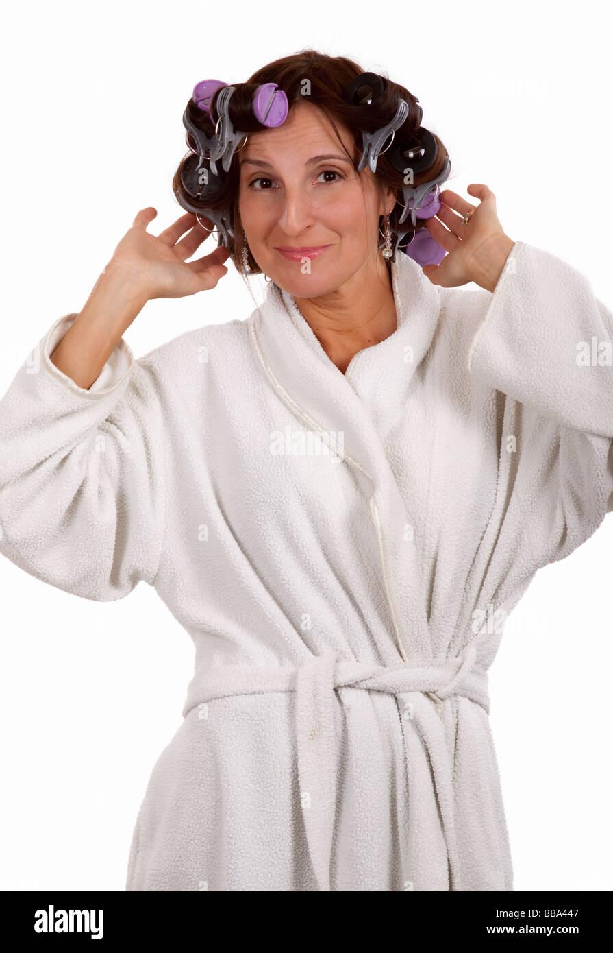 Femme en robe de chambre et bigoudis Photo Stock