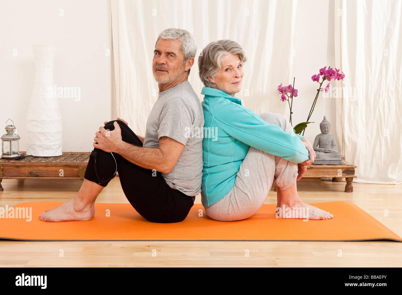 Droit assis dos à dos sur un tapis d'exercice Photo Stock