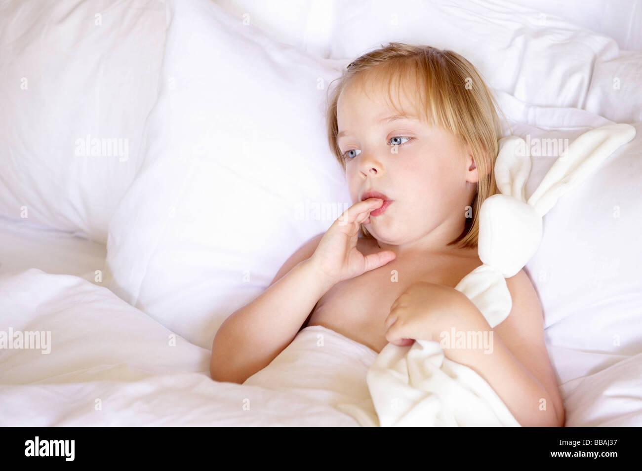 Fille dans le lit avec sa peluche préférée Photo Stock