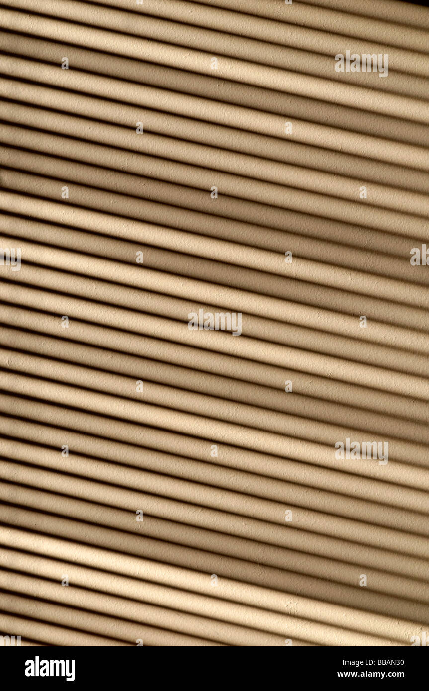 Ombre d'une fenêtre et une forte lumière du soleil tombant sur un mur à travers un store vénitien Photo Stock