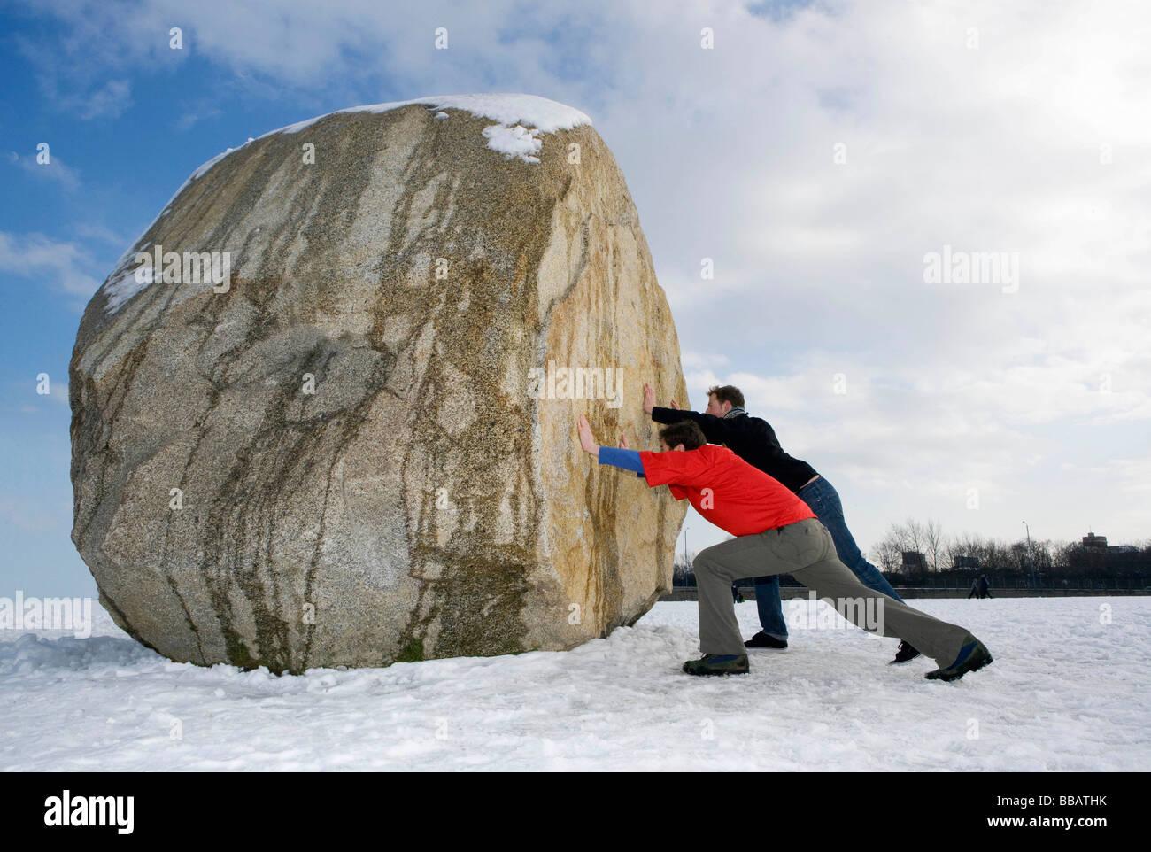 2 hommes poussant boulder massive Photo Stock