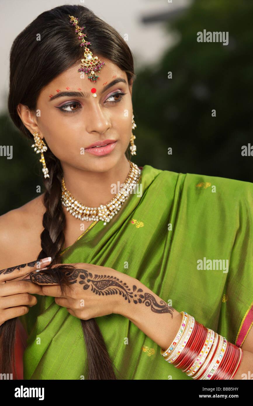Femme portant sari et décorées avec tatouage au henné, des bijoux traditionnels et bindi Photo Stock