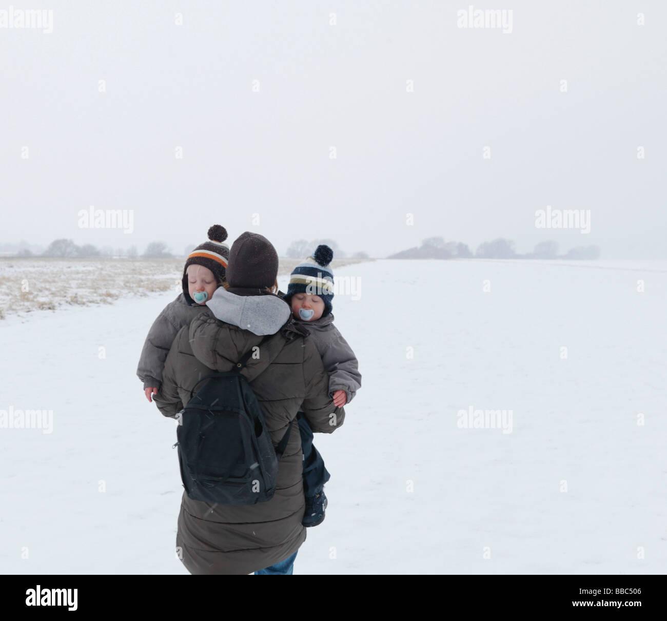 Femme marche avec deux fils jumeaux dans la neige Photo Stock