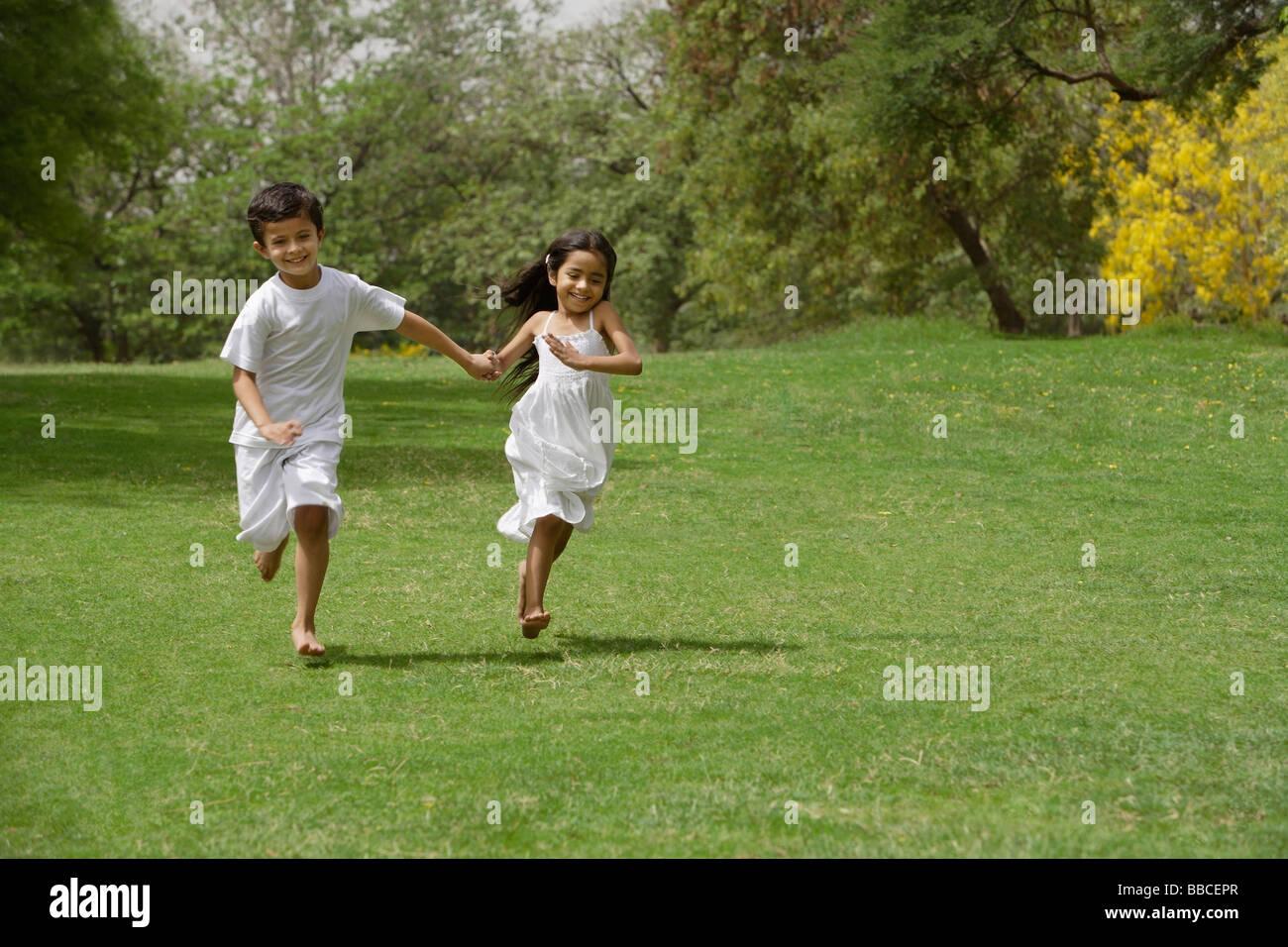 Enfants Qui Courent Dans Le Parc, Se Tenant La Main Banque