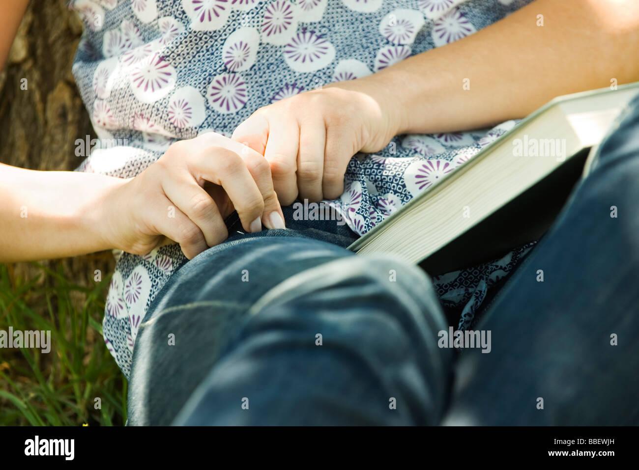 Jeune femme assise sur le sol avec le livre sur les genoux, pour atteindre quelque chose dans la poche Photo Stock