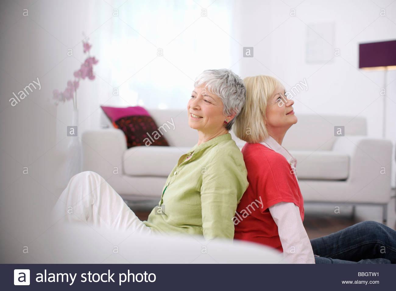 Les femmes âgées assis dos à dos salle de séjour Photo Stock