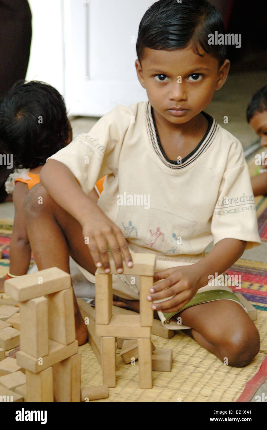 Jeune enfant dans l'un des nombreux bidonvilles de Chennai banlieue crèche; Inde, Tamil Nadu, Chennai (Madras) ... Banque D'Images