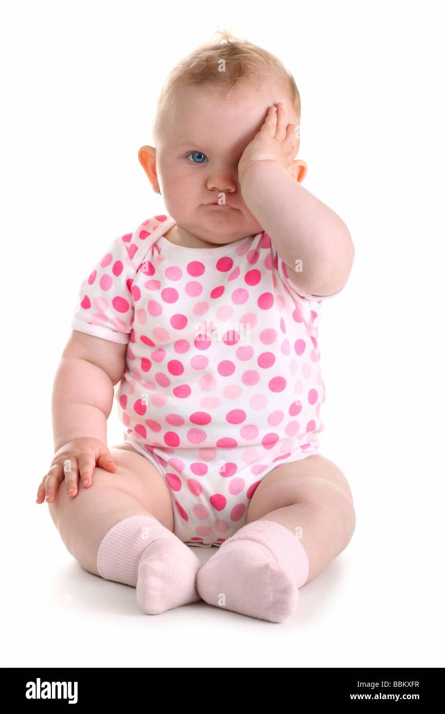 Little baby girl couvre l'œil avec la main gauche isolé sur blanc avec ombre Photo Stock