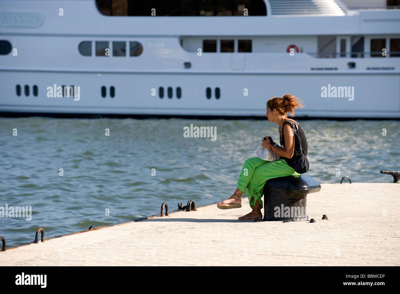 Fille assise sur un poste d'amarrage dans le port de La Havane, Cuba Photo Stock