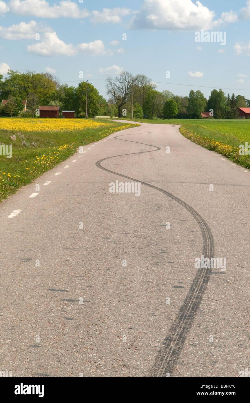 Route de campagne avec des marques de dérapage sur le tarmac Photo Stock