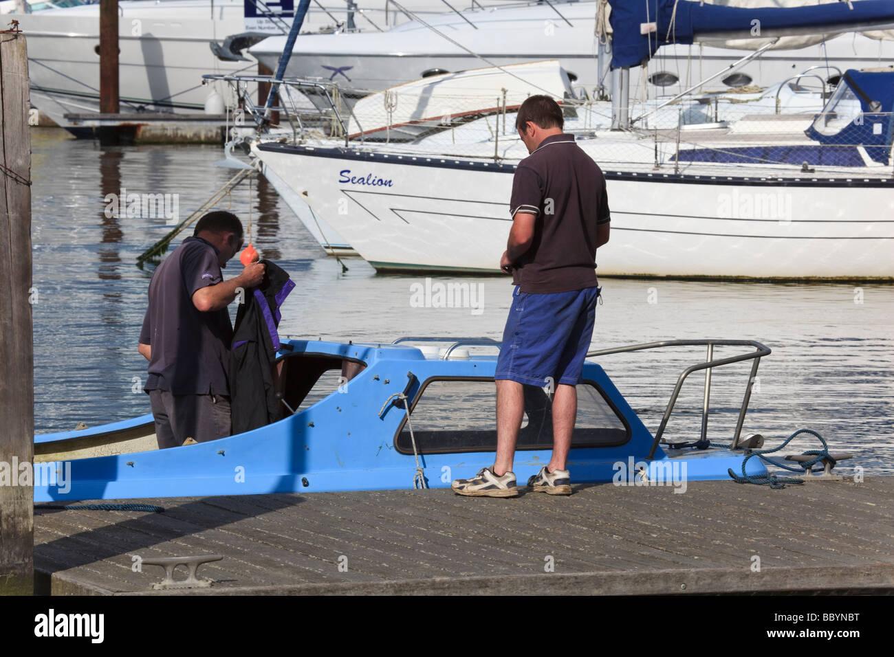 Deux hommes à bord d'une petite embarcation à moteur moor sur le ponton au Jolly Sailor Inn à Photo Stock