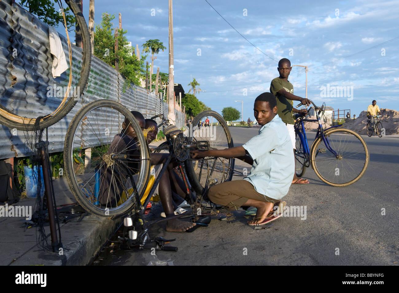 Les garçons l'exécution d'un atelier de réparation de bicyclettes dans les rues de Quelimane Photo Stock