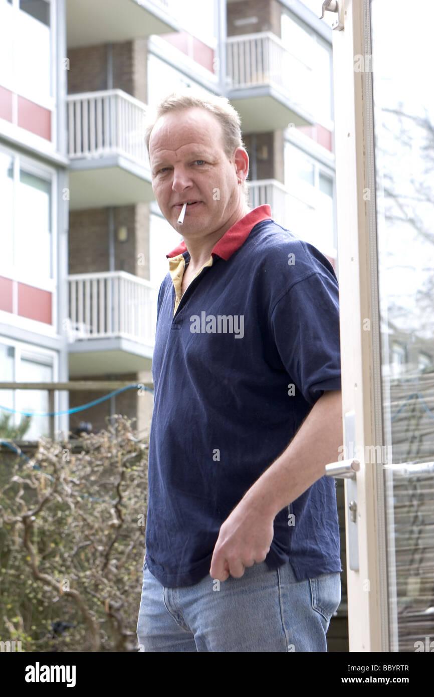 Malheureux homme d'âge moyen et l'expression grincheuse fumeurs sur balcon à l'extérieur Photo Stock