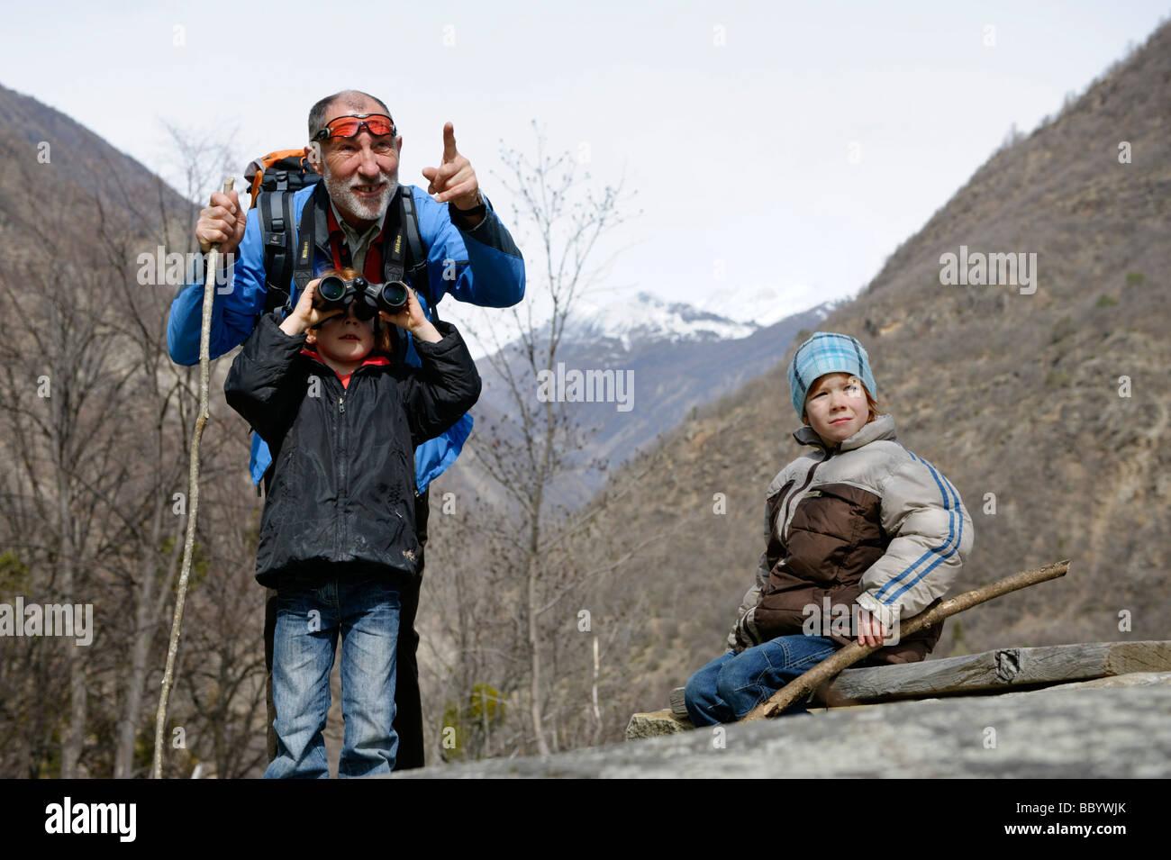 Grand-père montre à ses petits-enfants quelque chose avec ses jumelles Photo Stock