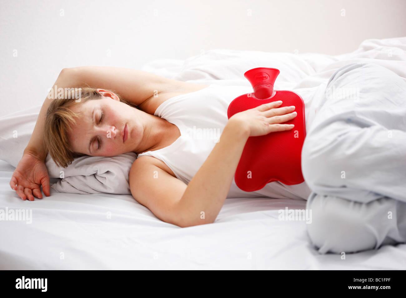 Femme a soulager la douleur à l'estomac avec un sac d'eau chaude chaudasse Photo Stock