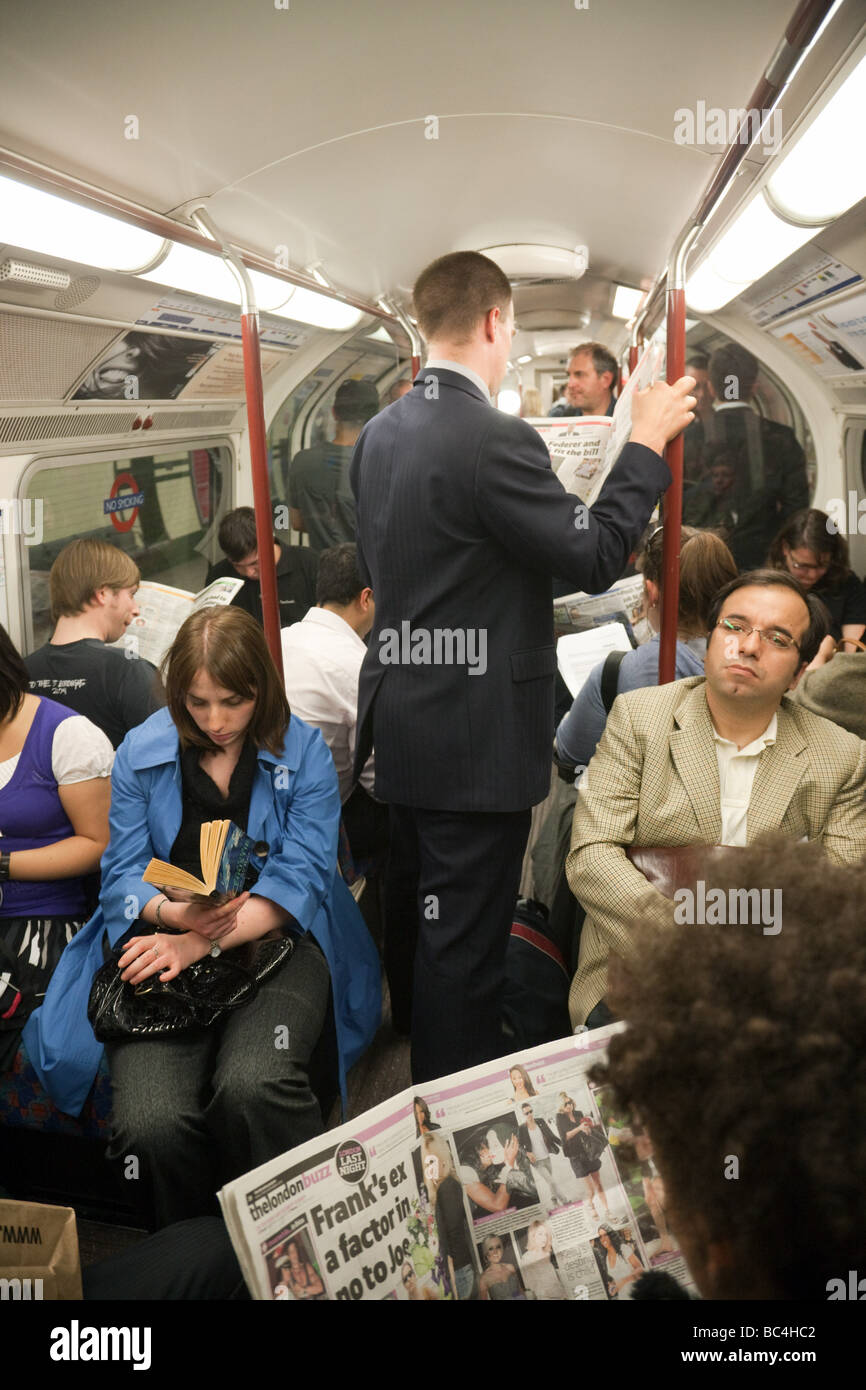 Les gens se tenant sur un train de métro bondé, London, UK Photo Stock