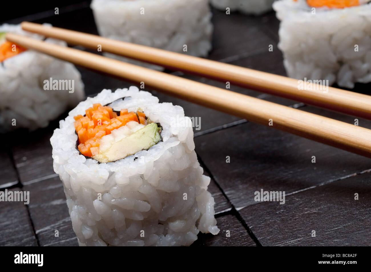 Une faible profondeur horizontale inclinée focus macro de sushi avec copsticks sur un fond en bois noir Photo Stock