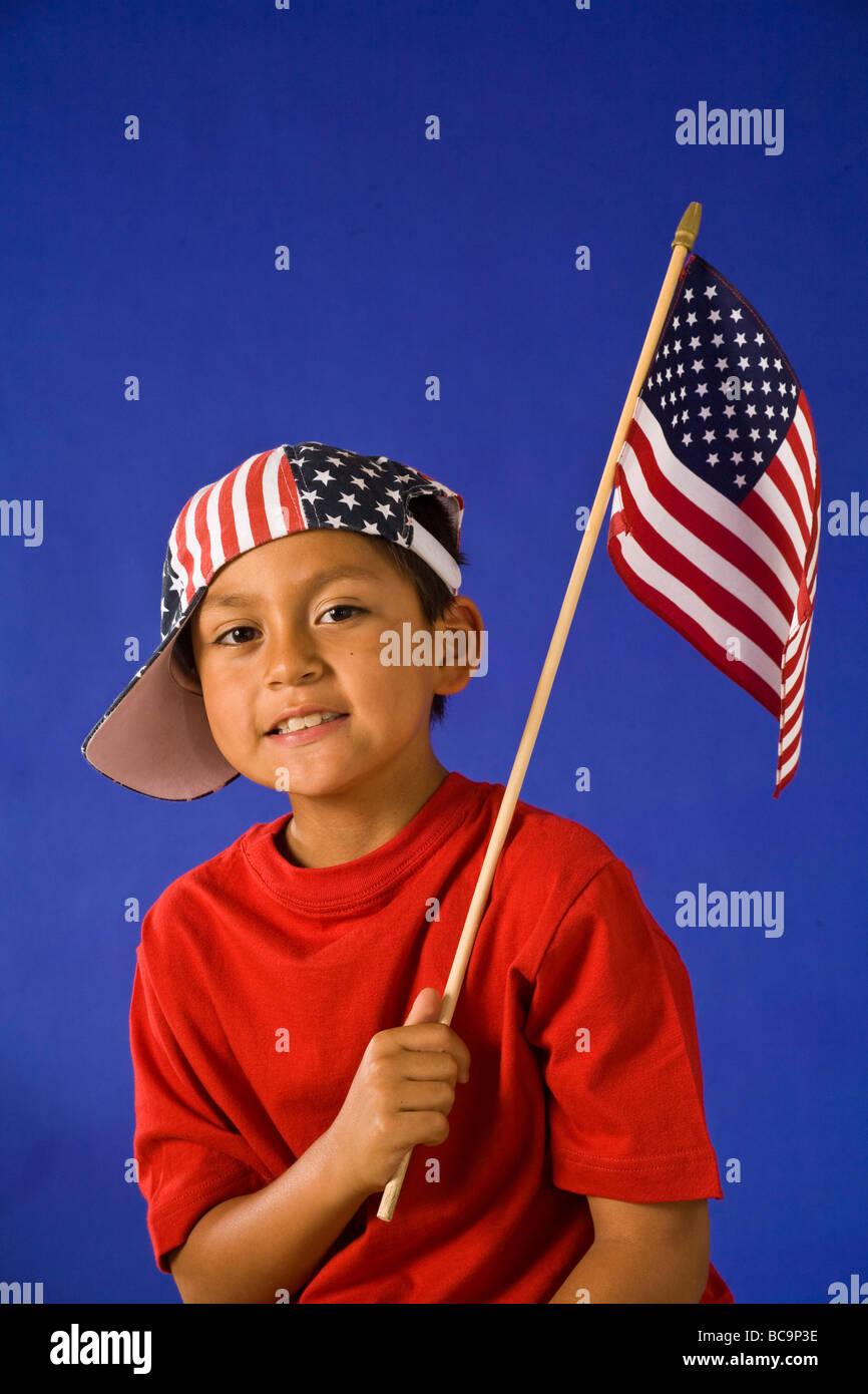 Portrait of boy défilé du 4 juillet forme holding American flag et souriant M. © Myrleen Pearson Banque D'Images