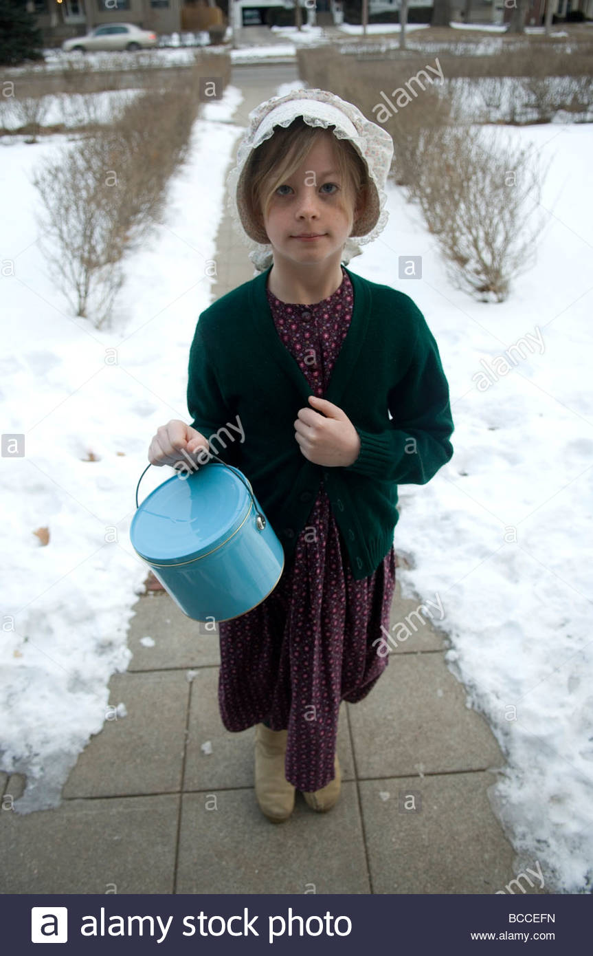 Une jeune fille se prépare pour l'École du patrimoine dans un tournant du siècle robe. Photo Stock