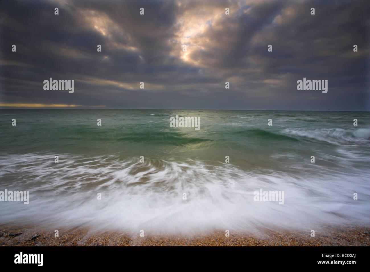 L'action des vagues et l'approche de l'orage. Lieu non identifié de sables bitumineux. Devon Photo Stock