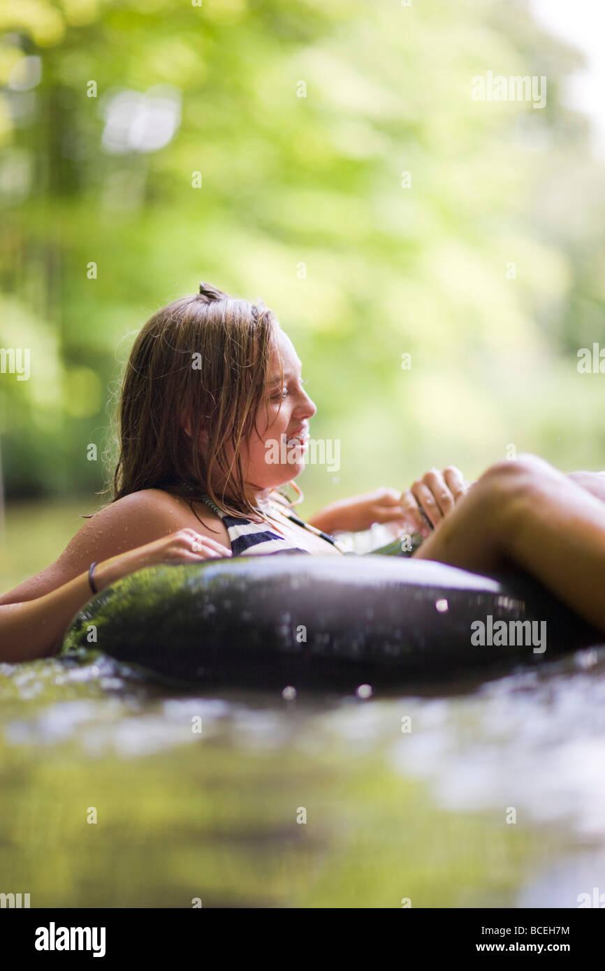 Les adolescents assis dans innertubes dans l'eau Photo Stock