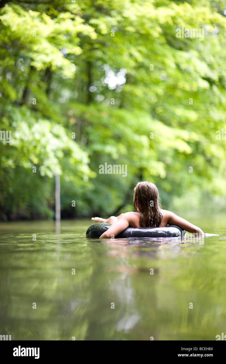 Fille assise seule dans l'eau dans une chambre à air Photo Stock
