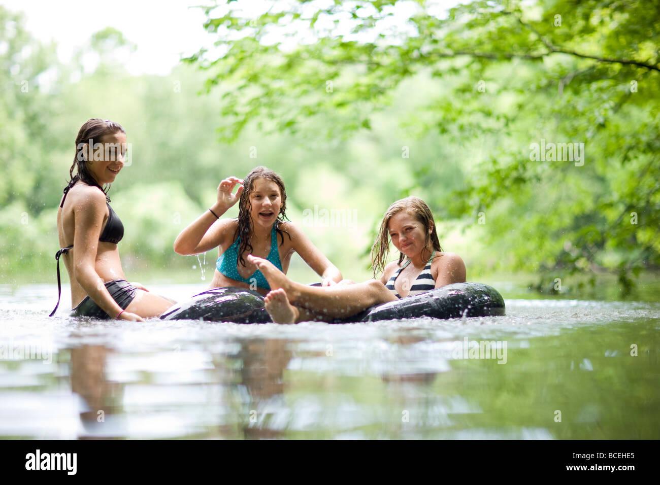 Les adolescents s'amusant dans innertubes dans l'eau Photo Stock
