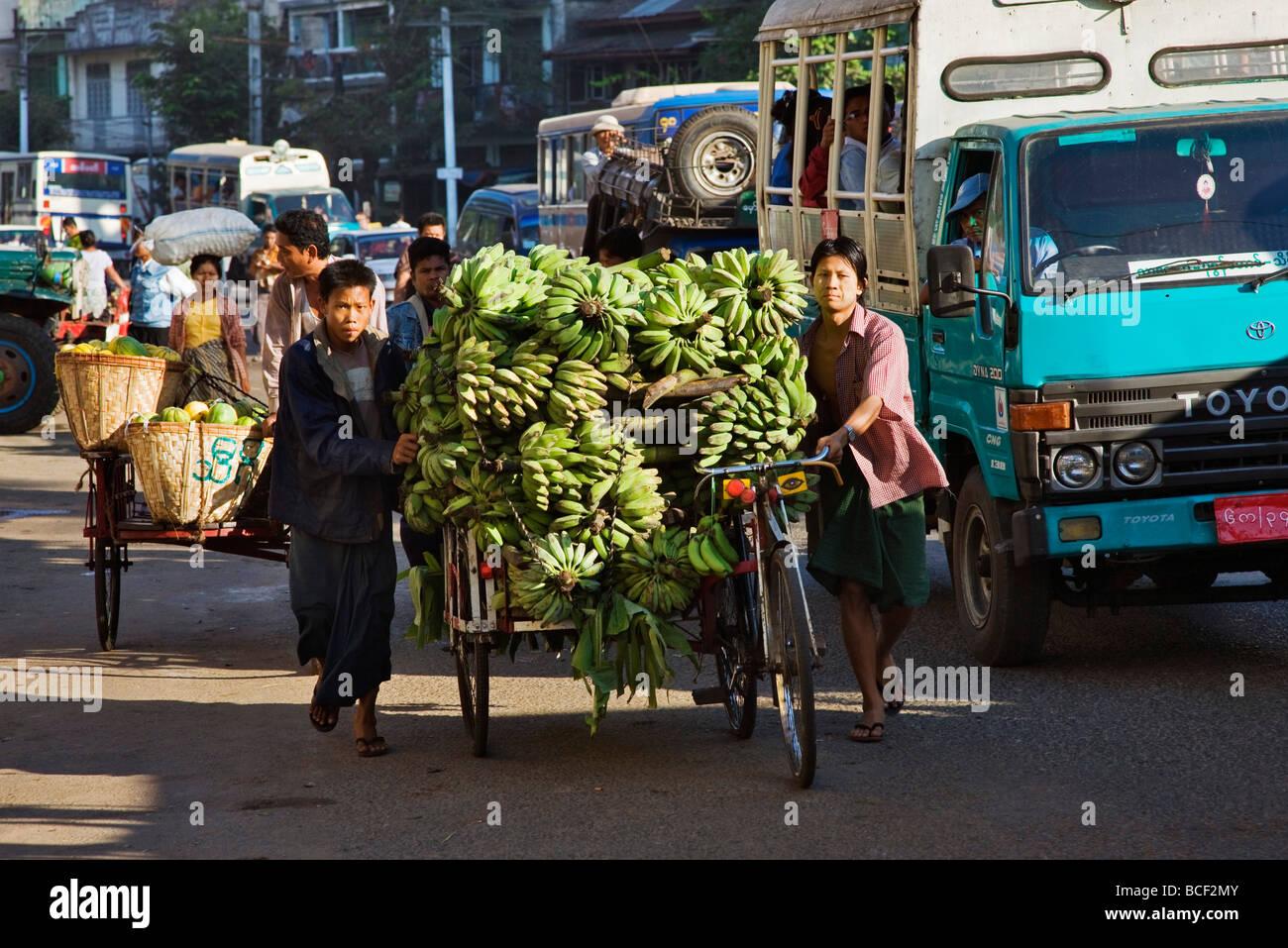 Le Myanmar, Birmanie, Yangon. Une longue scène de rue à Yangon avec trishaws laden avec fruit la position de marché. Banque D'Images