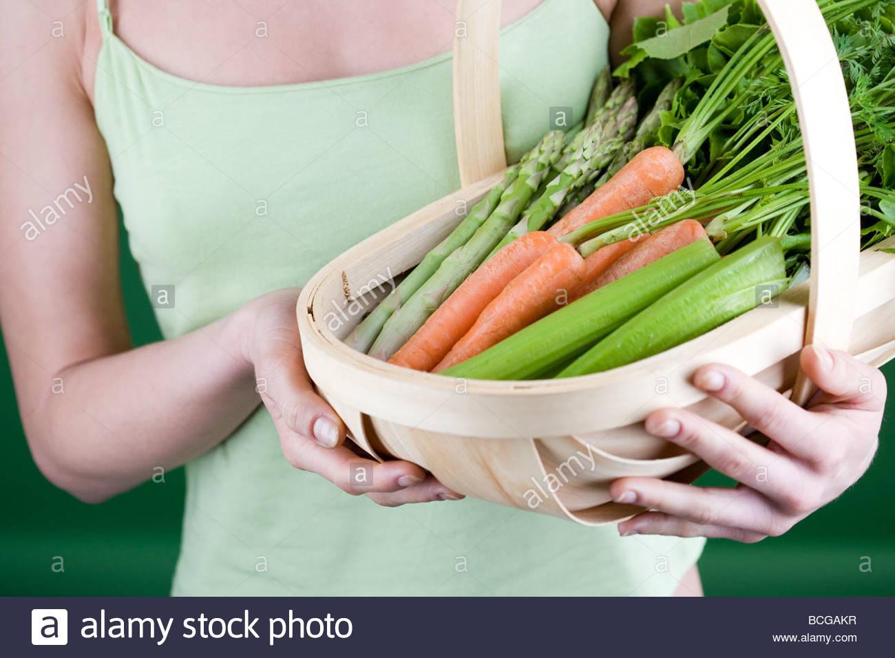 Une jeune femme tenant un panier plein de légumes Photo Stock