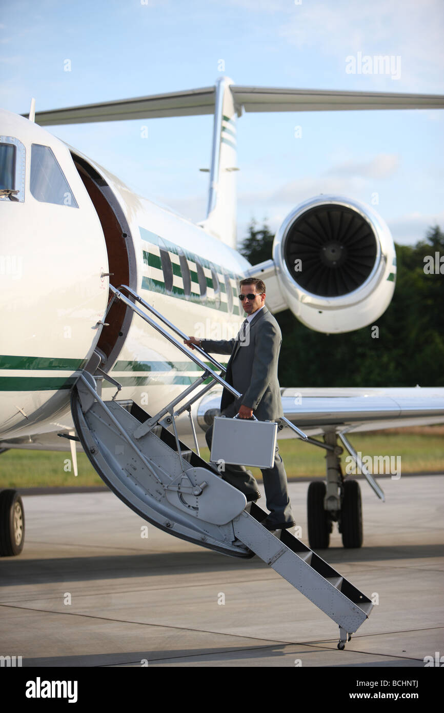 Businessman standing on stairs à Private Jet Photo Stock