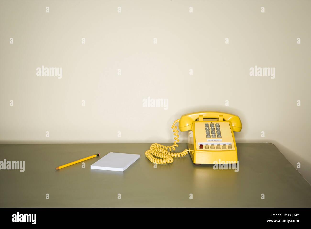 Téléphone jaune assis sur bureau métallique en face de mur blanc