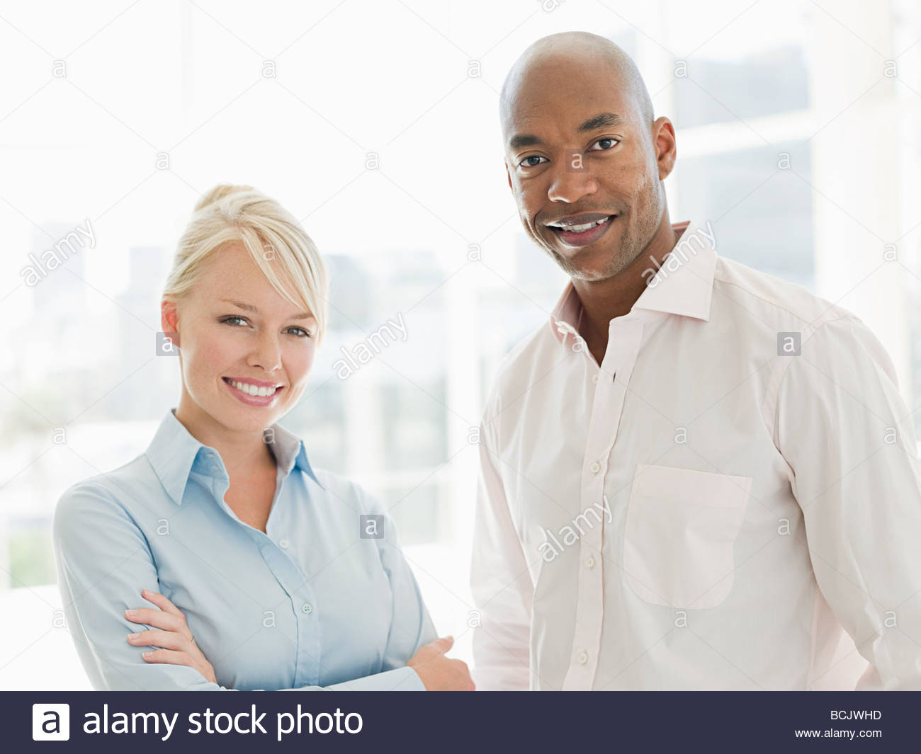 Young businesswoman and businessman standing in office Photo Stock