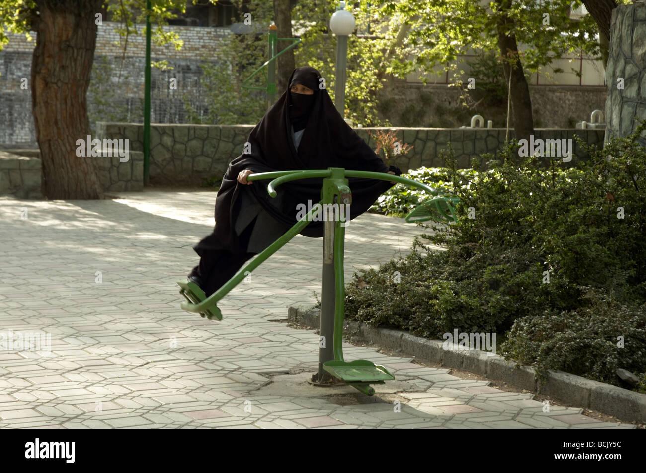 Femme en burqa sur une machine d'exercice à Téhéran Photo Stock