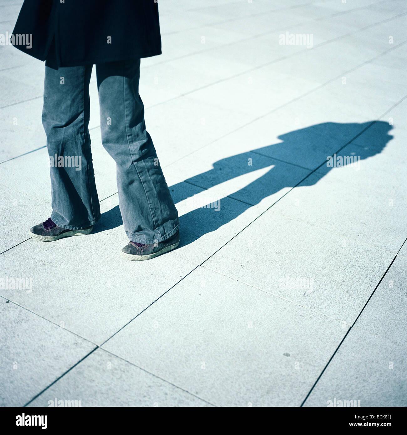La partie inférieure de la personne et l'ombre sur le sol Photo Stock