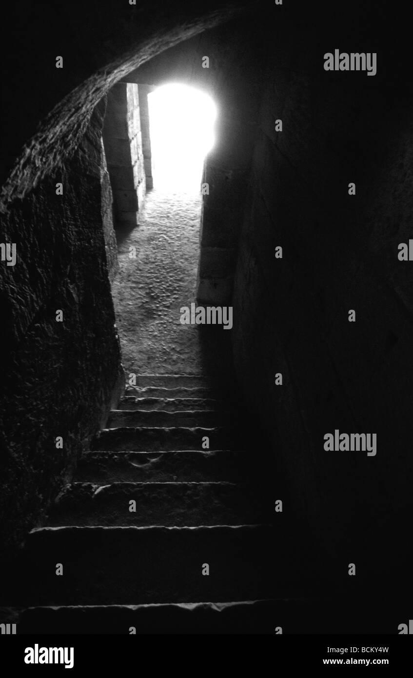 Escalier sombre avec la lumière provenant de la porte, blanc et noir. Photo Stock