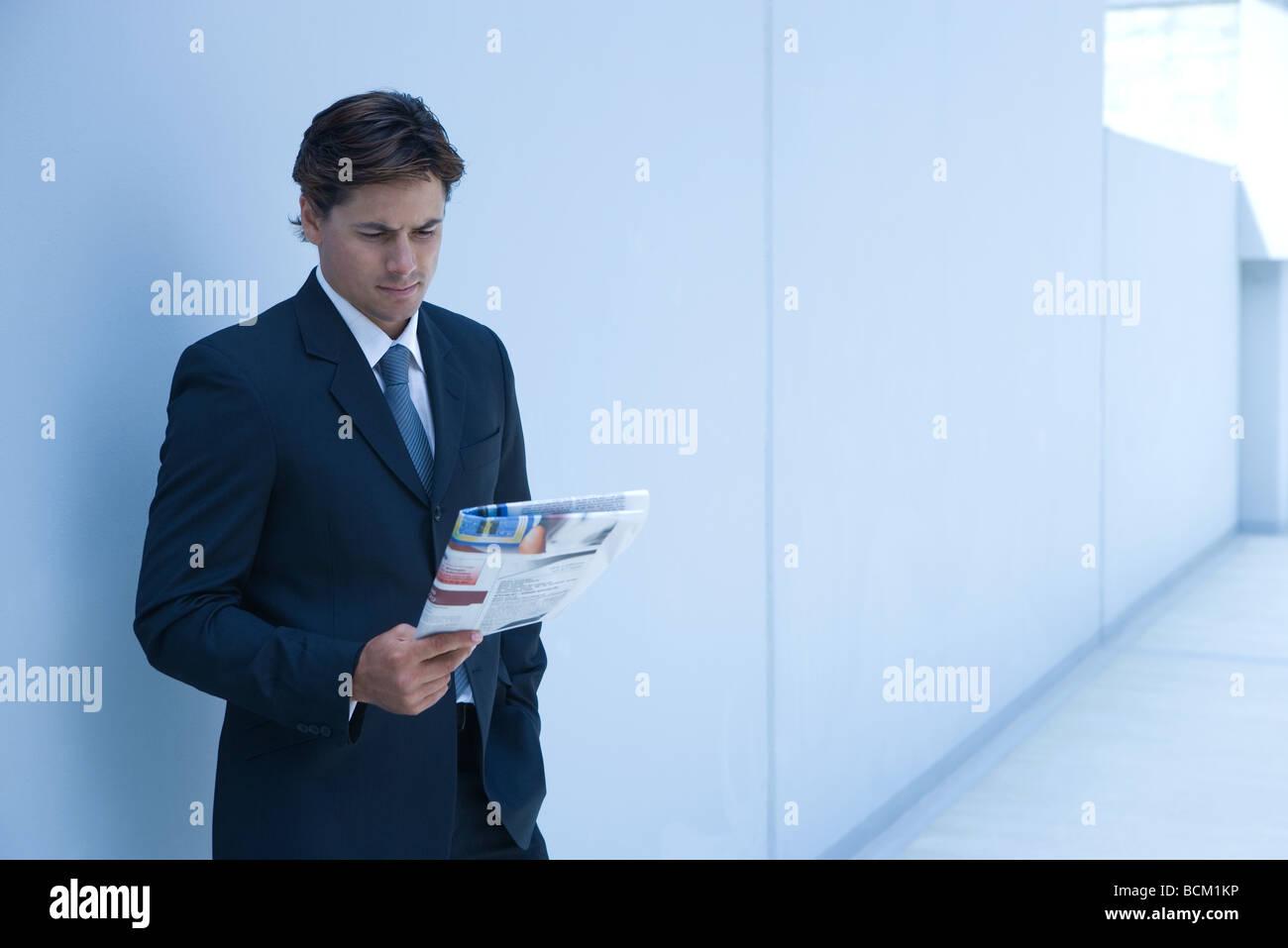 Businessman standing, reading newspaper Photo Stock