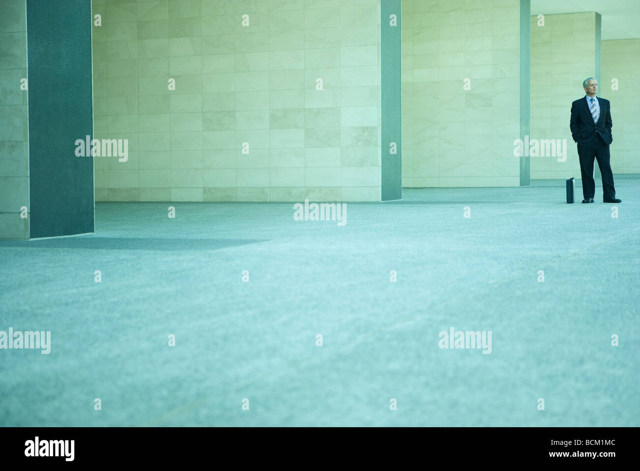 Businessman standing next to porte-documents avec les mains dans les poches, à la mi-distance, pleine longueur Photo Stock