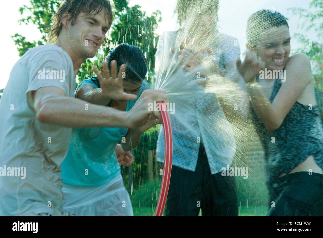 Jeunes amis d'avoir de l'eau lutte avec tuyau de jardin Photo Stock