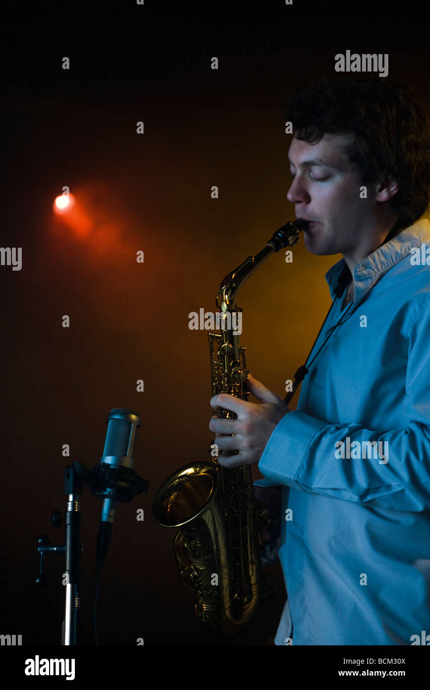 Young man playing saxophone dans night club Photo Stock