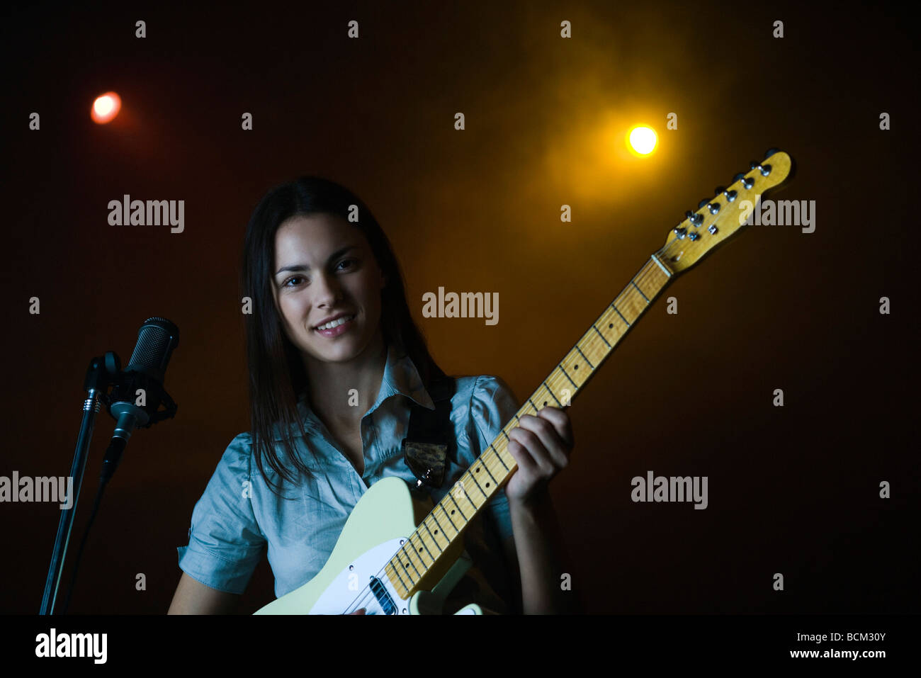 Jeune femme jouant de la guitare électrique, smiling at camera Photo Stock