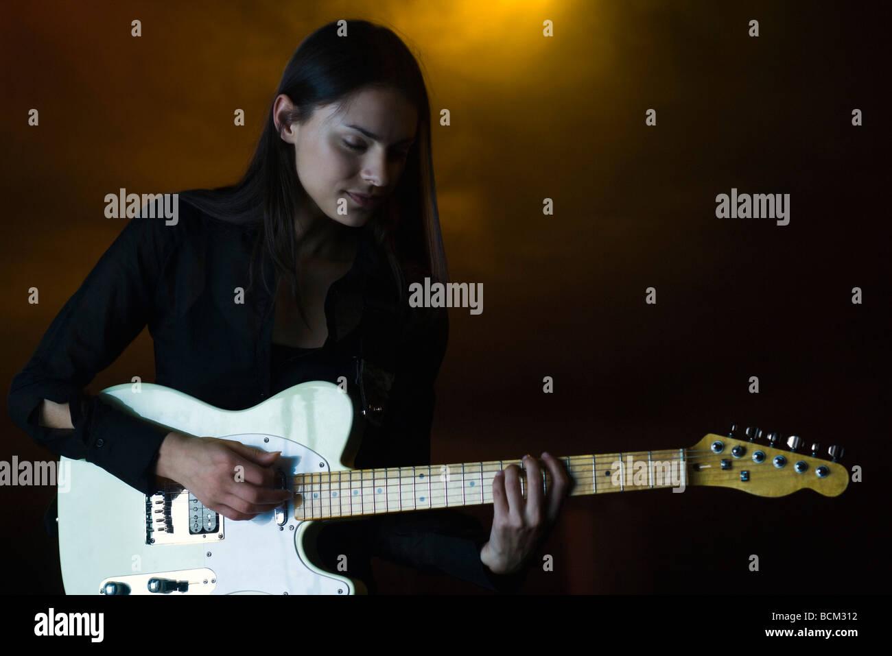 Femme jouant de la guitare électrique dans une boîte de nuit, les yeux fermés Photo Stock