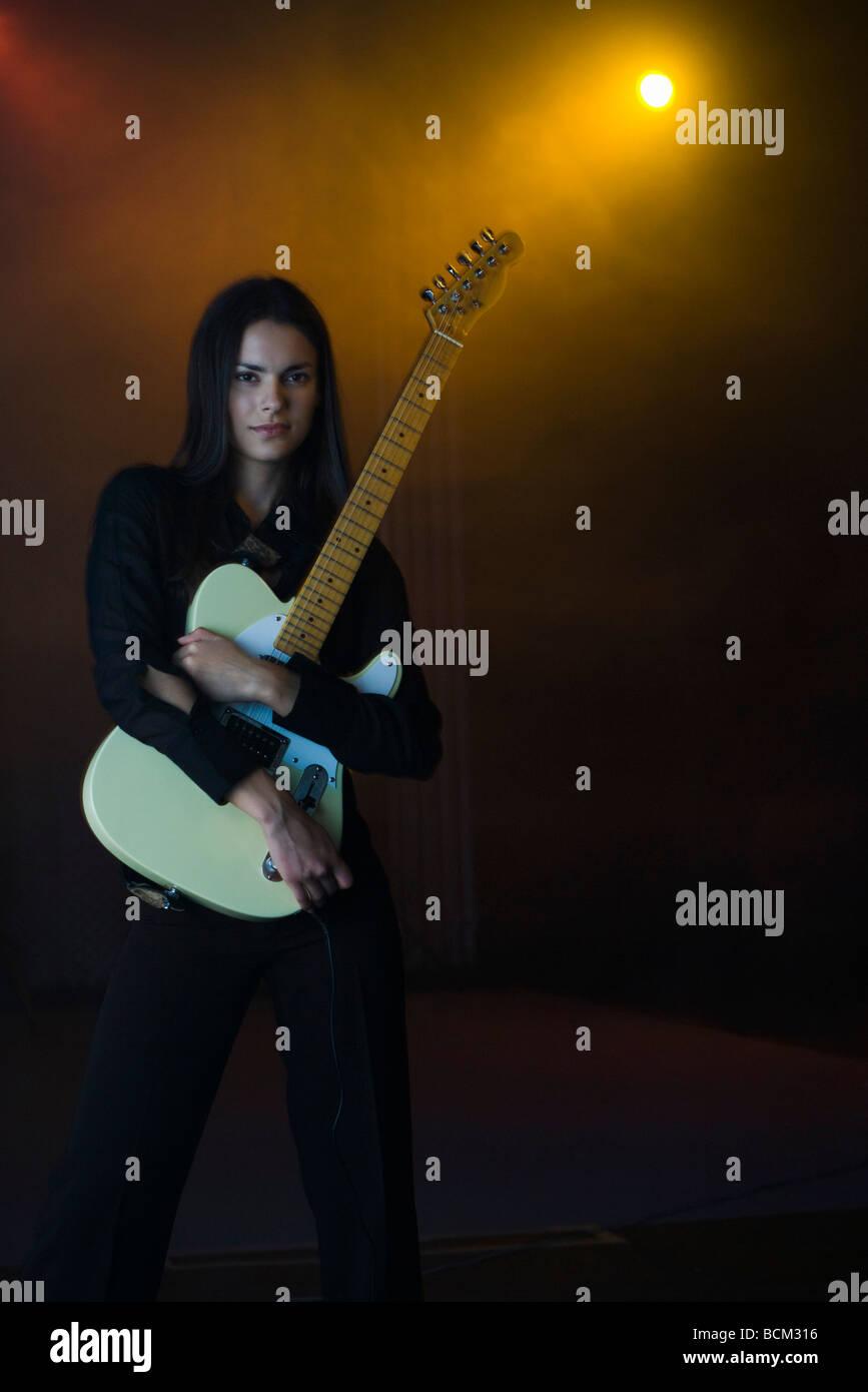 Femme tenant une guitare électrique, portrait Photo Stock