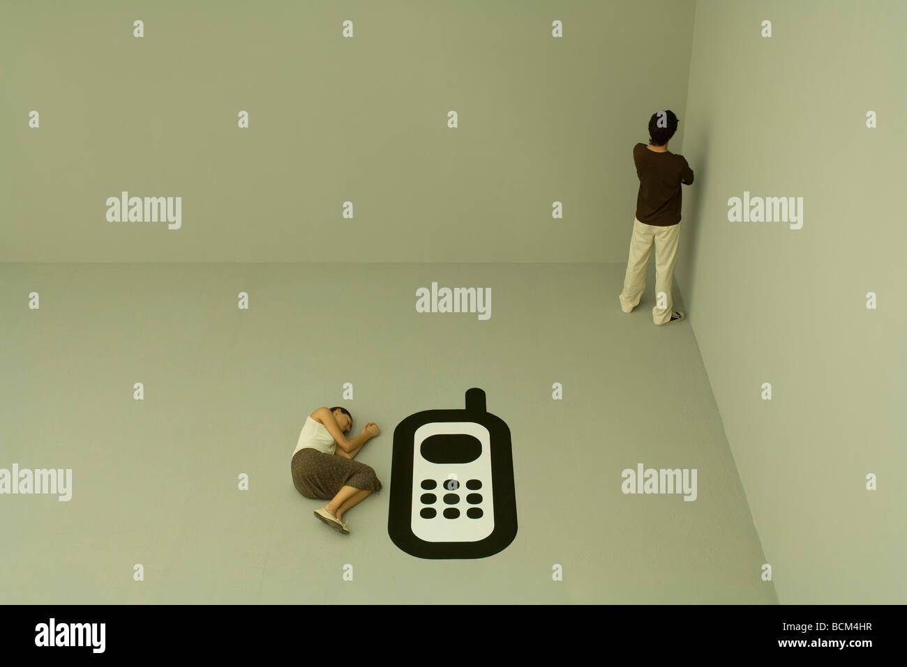 Femme couchée sur le sol à côté d'un grand téléphone portable, homme debout à corner Banque D'Images