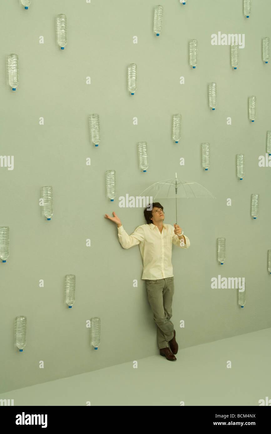 Man holding umbrella, bouteilles d'eau tombent comme des gouttes de pluie autour de lui Photo Stock