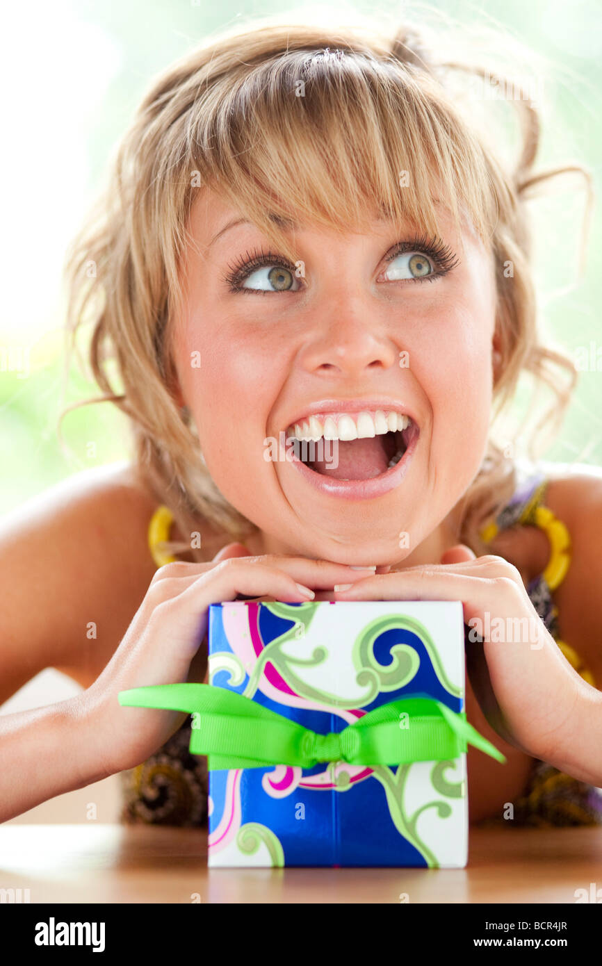 Girl leaning on wrapped present Photo Stock