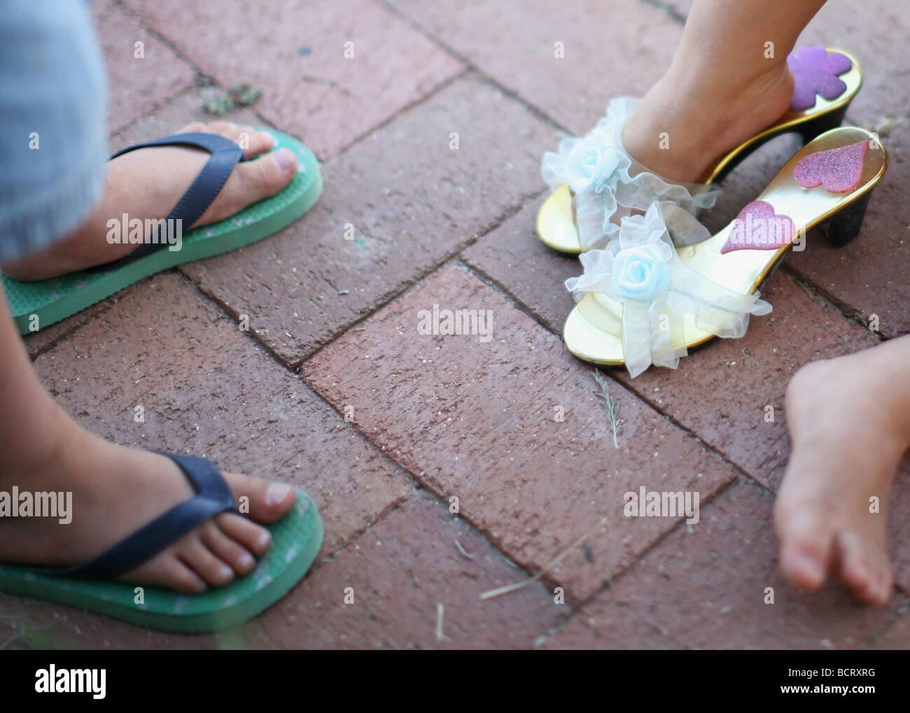 La section basse de deux enfants portant des chaussons et sandales Photo Stock