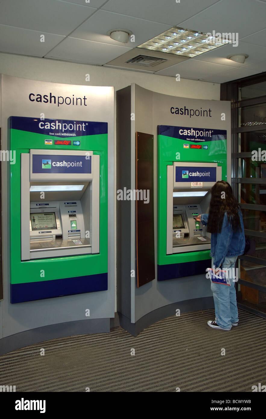 Femme à l'aide de la Lloyds TSB Bank distributeur, Christchurch, Dorset, England, UK Banque D'Images