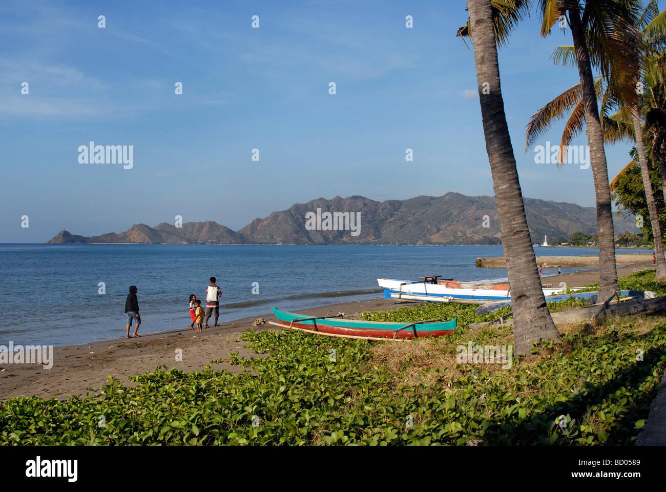 Une famille promenade le long de la plage de Dili, capitale du Timor Leste Banque D'Images