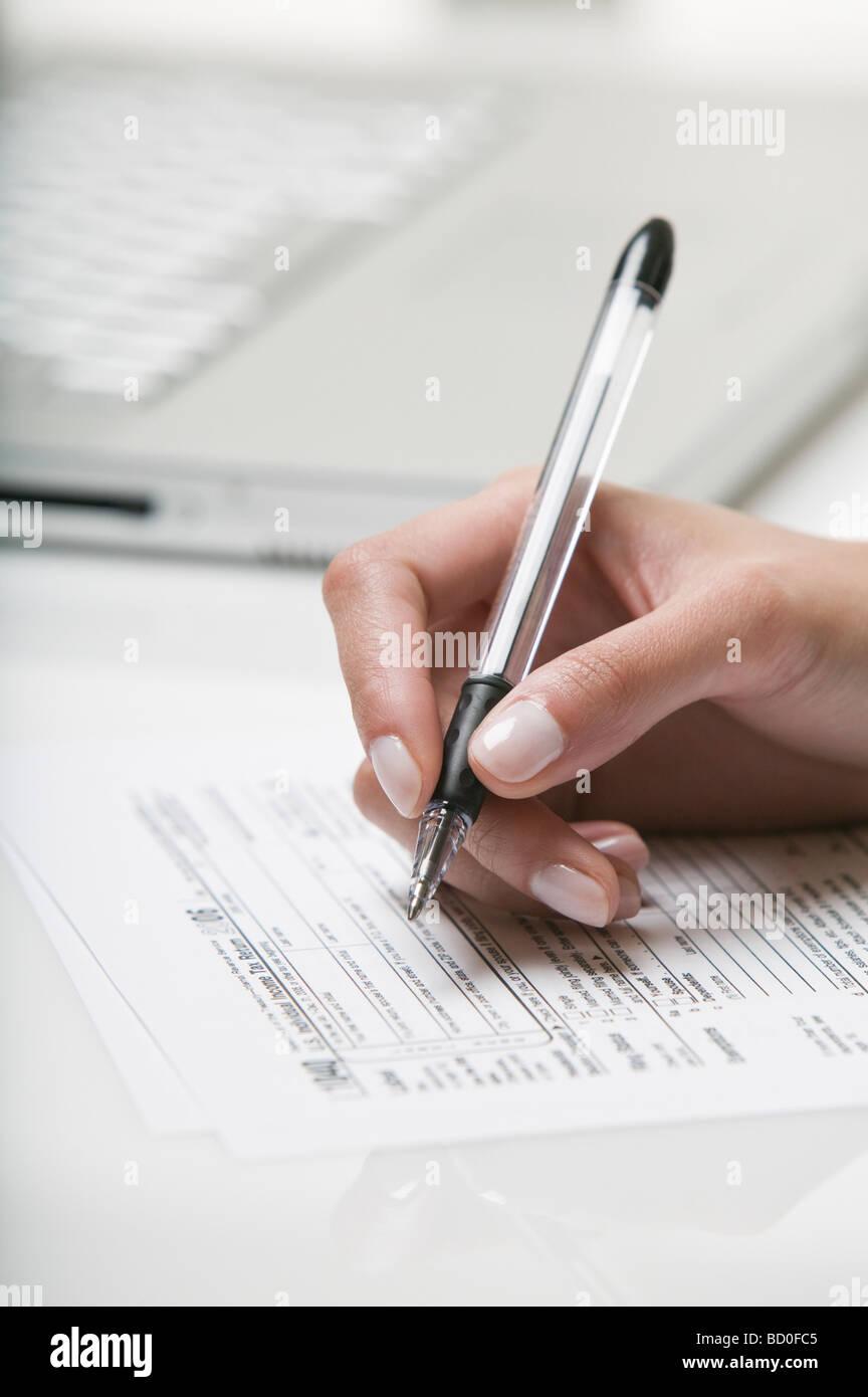 Femme remplissant un formulaire d'impôt Photo Stock